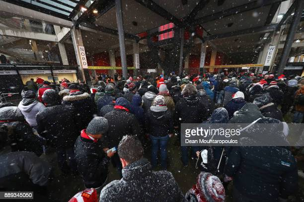 Fans arrive as the heavy snow falls prior to the Bundesliga match between 1 FC Koeln and SportClub Freiburg at RheinEnergieStadion on December 10...