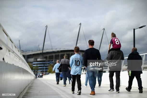 Fans arrive at the stadium prior to the Premier League match between Manchester City and Crystal Palace at Etihad Stadium on September 23 2017 in...