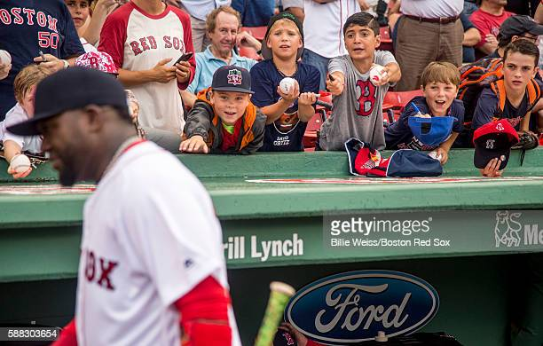 Fans ask for autographs from David Ortiz of the Boston Red Sox before a game against the New York Yankees on August 10 2016 at Fenway Park in Boston...