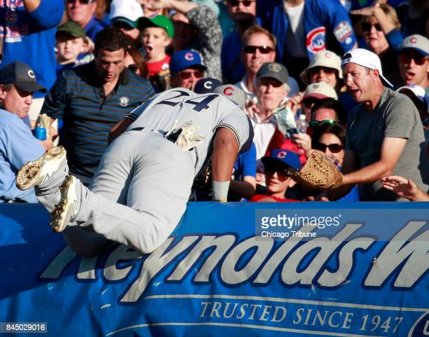 Fans ask Milwaukee Brewers first baseman Jesus Aguilar for the ball after he had caught it in foul territory during the seventh inning against the...