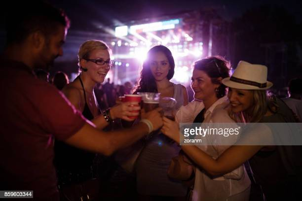 Fans at concert toasting with beer