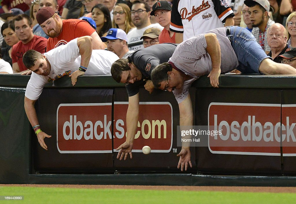 Fans attempt to catch a foul ball during a game between the Arizona Diamondbacks and the San Diego Padres at Chase Field on May 24, 2013 in Phoenix, Arizona.