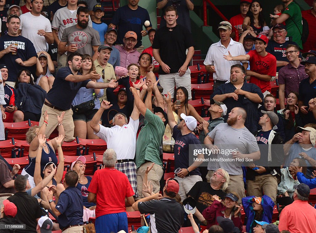 Fans attempt to catch a foul ball during a game between the Boston Red Sox and the Colorado Rockies in the ninth inning on June 26, 2013 at Fenway Park in Boston, Massachusetts.