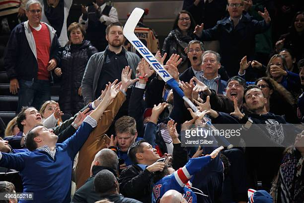 Fans battle the stick of Henrik Lundqvist of the New York Rangers after he throws it into the crowd following his shutout against the Carolina...