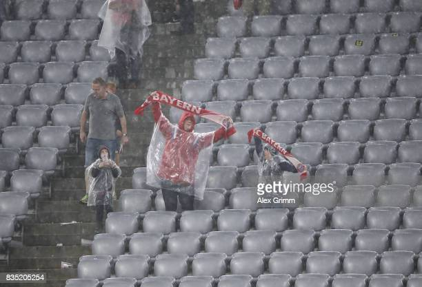 Fans brave the rain and bad weather during the Bundesliga match between FC Bayern Muenchen and Bayer 04 Leverkusen at Allianz Arena on August 18 2017...
