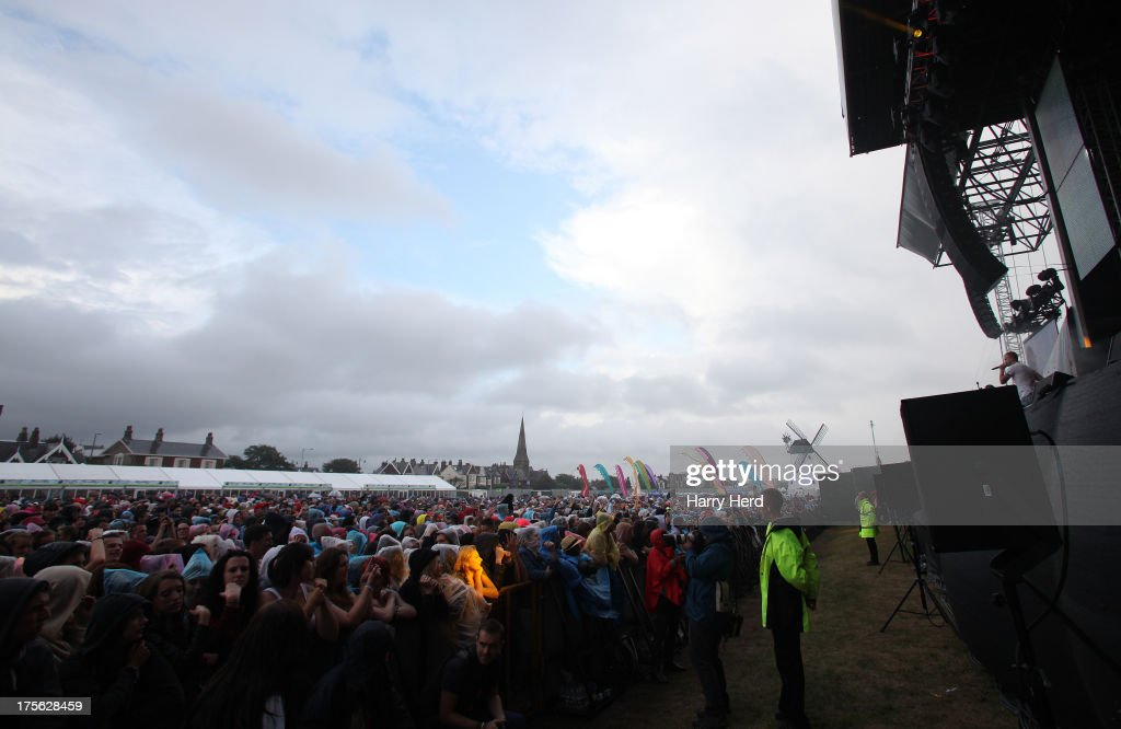 Fans brave the weather as Ed Drewett performs on stage at Lytham Proms at Royal Lytham & St. Annes on August 4, 2013 in Lytham St Annes, England.
