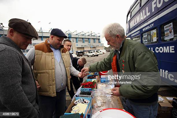 Fans buy Remembrance Day commemorative pins ahead of the Sky Bet Championship match between Millwall and Brentford at The Den on November 8 2014 in...