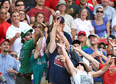 Fans catch a foul ball during a game betweenthe Boston Red Sox and the Seattle Mariners in the sixth inning at Fenway Park on August 15 2015 in...