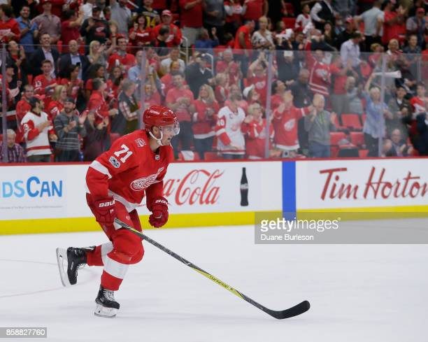 Fans celebrate a goal by Dylan Larkin of the Detroit Red Wings during the second period of a game against the Minnesota Wild at Little Caesars Arena...