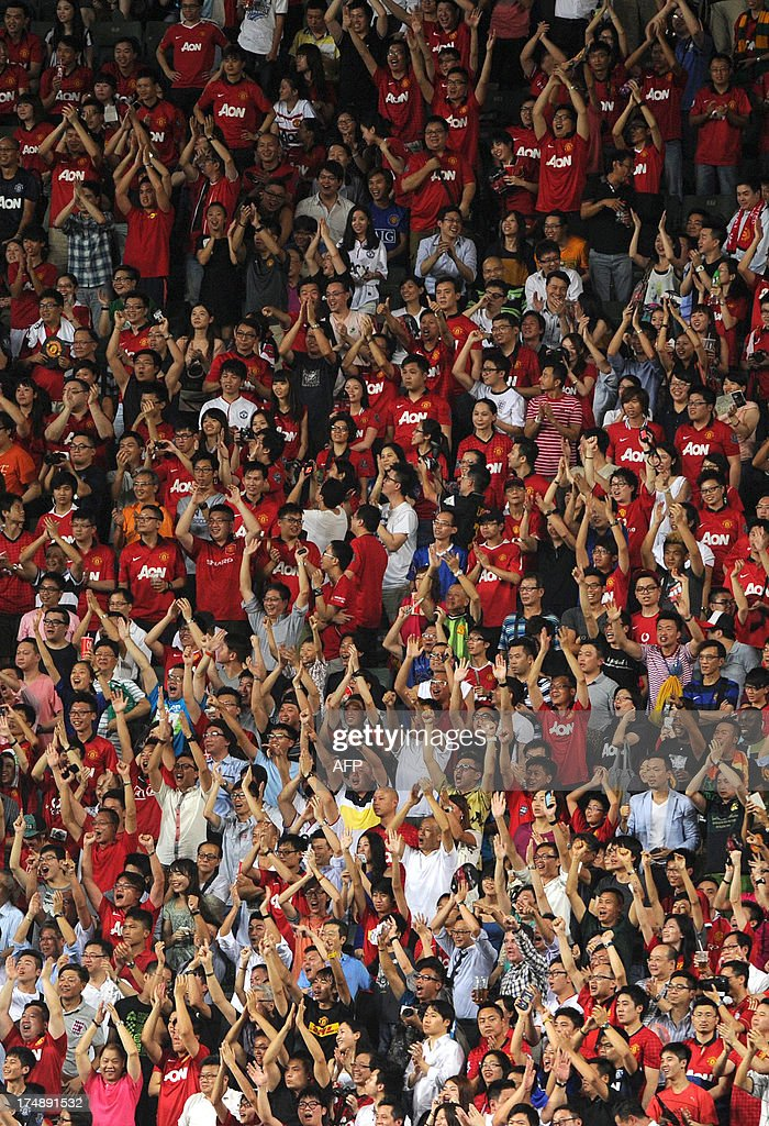 Fans celebrate a goal during a football friendly match between English Premier League, Manchester United and Kitchee at Hong Kong stadium on July 29, 2013. AFP PHOTO / Dale de la Rey