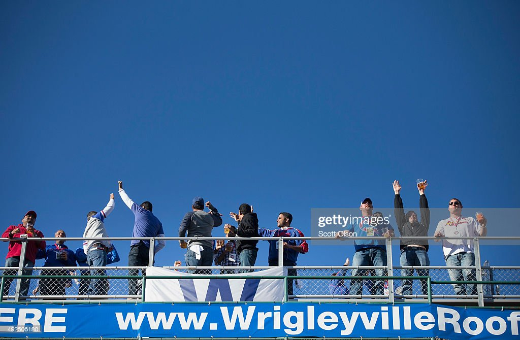 Fans celebrate a second-inning home run as they watch from the roof of a building across from Wrigley Field as the Chicago Cubs play the St. Louis Cardinals in game four of the NLDS championship series at the park on October 13, 2015 in Chicago, Illinois. The Cubs lead the series 2-1.