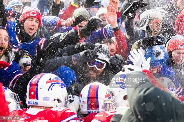 Fans celebrate above players after LeSean McCoy of the Buffalo Bills scores the game winning touchdown in overtime against the Indianapolis Colts at...