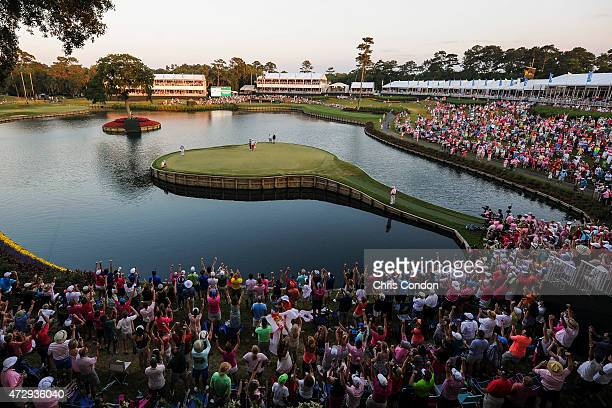 Fans celebrate as Rickie Fowler sinks a winning birdie putt on the 17th hole island green during a sudden death playoff in the final round of THE...