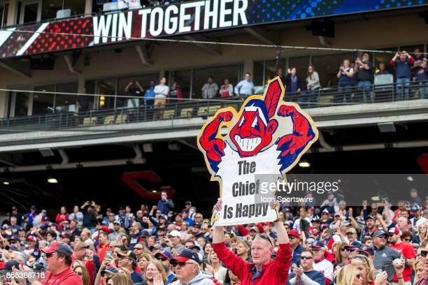 Fans celebrate behind the Indians dugout after the Indians recored their 100th victory of the season following the Major League Baseball game between...