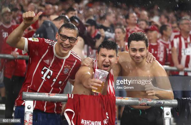 Fans celebrate even in the rain and bad weather during the Bundesliga match between FC Bayern Muenchen and Bayer 04 Leverkusen at Allianz Arena on...