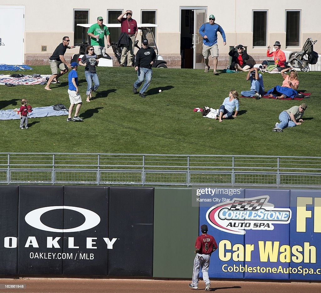 Fans chase after the home run ball hit by the Kansas City Royals' Max Ramirez, as Arizona Diamondbacks left fielder Adam Eaton (6) looks on, in the fifth inning of a spring training game in Surprise, Arizona, Monday, February 25, 2013. The Royals beat the Diamondback, 16-4.