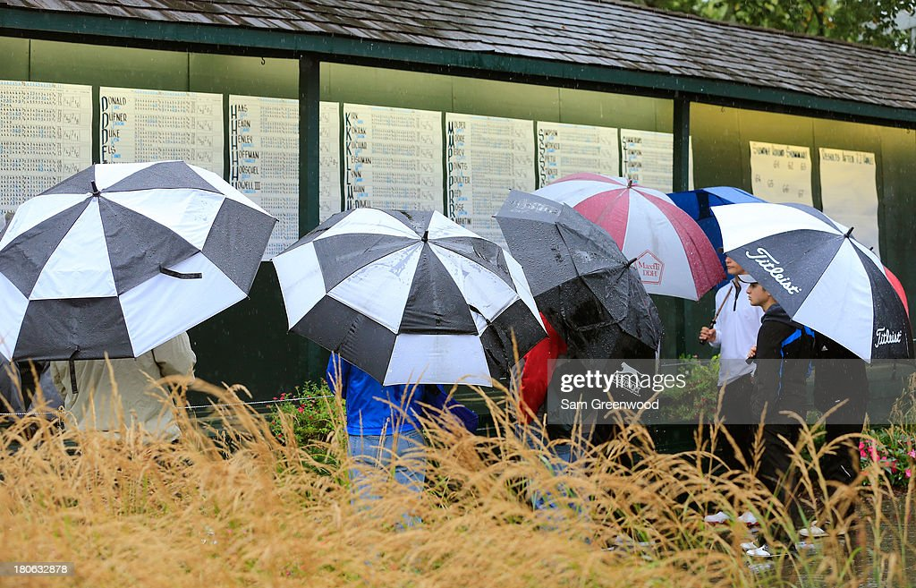Fans check the leaderboard under umbrellas as play is suspended due to inclement weather during the Final Round of the BMW Championship at Conway Farms Golf Club on September 15, 2013 in Lake Forest, Illinois.