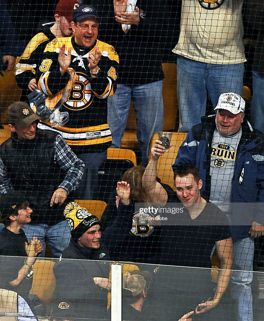 Fans cheer a fellow patron who appeared to have caught a puck that went flying into the stands in his cup as the Boston Bruins hosted the Winnipeg Jets in an NHL regular season game at the TD Garden.