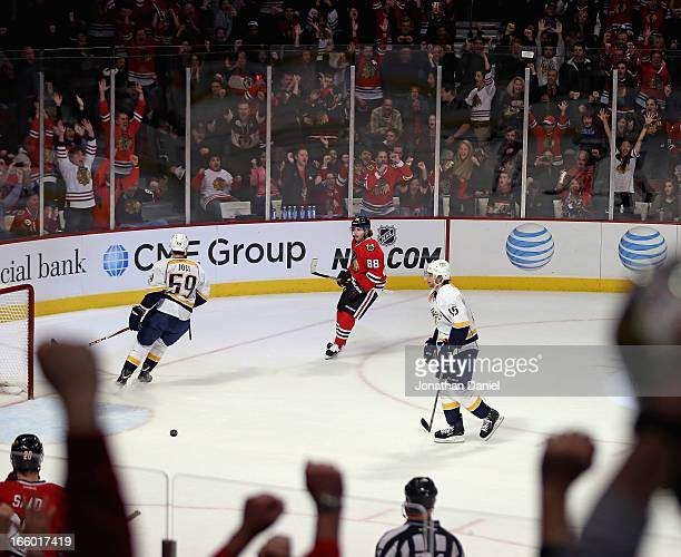 Fans cheer after Patrick Kane of the Chicago Blackhawks scores an empty net goal as Roman Josi and Craig Smith of the Nashville Predators try to...