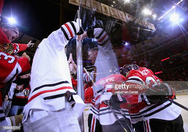 Fans cheer and pound on the glass as members of the Chicago Blackhawks celebrate a third period goal by Andrew Shaw against the Detroit Red Wings in...
