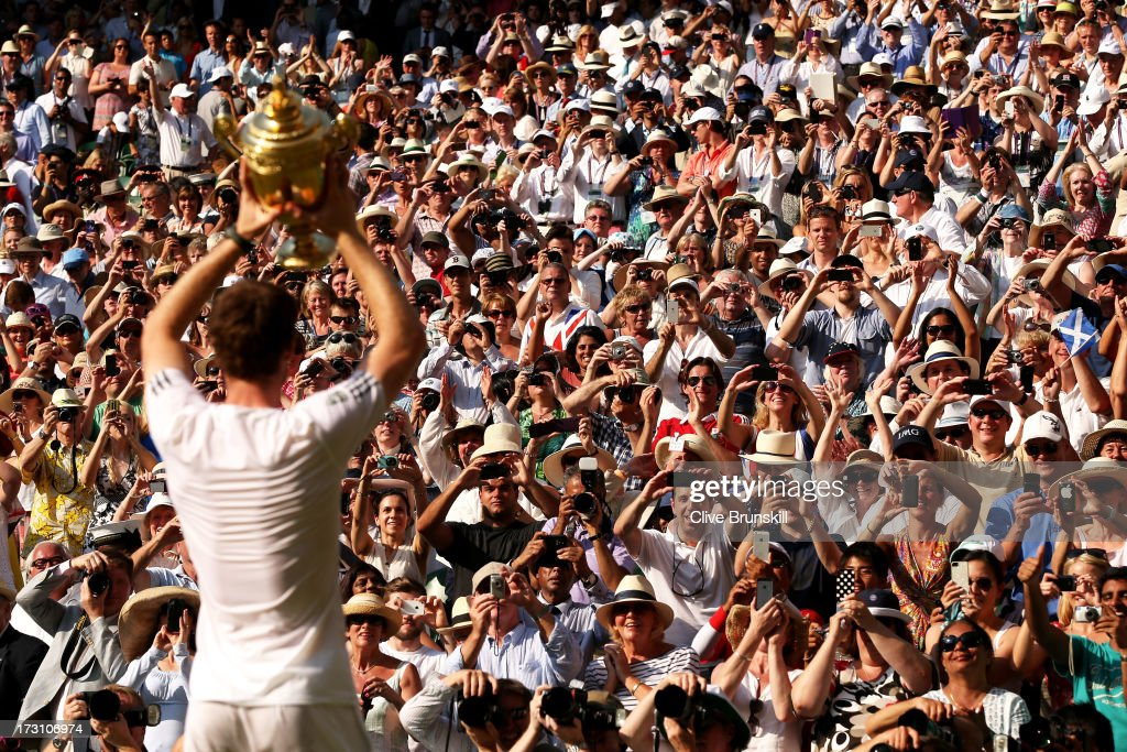 Fans cheer and take photographs as Andy Murray of Great Britain poses with the Gentlemen's Singles Trophy following his victory in the Gentlemen's...
