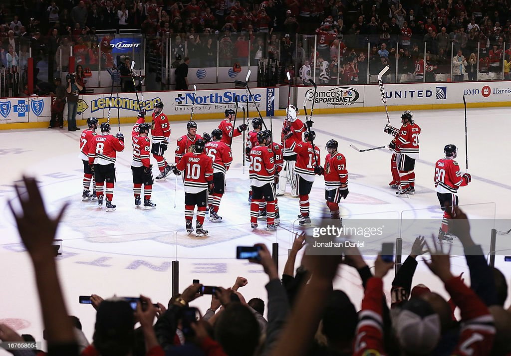 Fans cheer and take pictures as members of the Chicago Blackhawks salute the crowd following a win over the Calgary Flames at the United Center on April 26, 2013 in Chicago, Illinois. The Blackhawks defeated the Flames 3-1.
