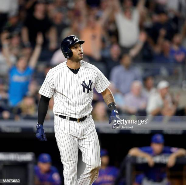 Fans cheer as Aaron Hicks of the New York Yankees watches his home run as he starts up the first base line in an MLB baseball game against the New...
