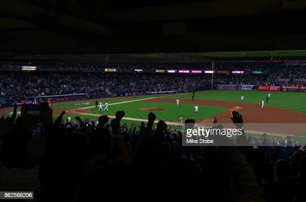 Fans cheer as Aroldis Chapman of the New York Yankees celebrates with Gary Sanchez after defeating the Houston Astros in Game Four of the American...
