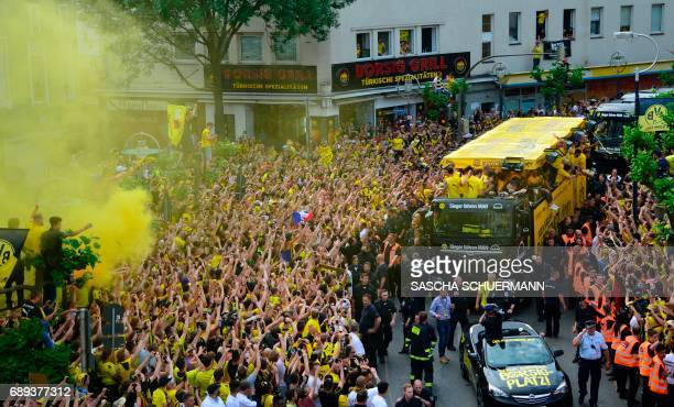 Fans cheer as Borussia Dortmund arrive players at Borsigplatz during celebrations after winning the German Cup final in Dortmund western Germany on...