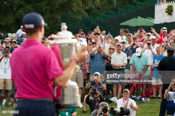 Fans cheer as Champion Justin Thomas holds the Wanamaker Trophy at the Awards Ceremony during the Final Round for the 99th PGA Championship held at...