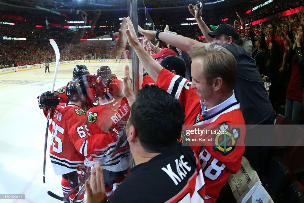 Fans cheer as Dave Bolland of the Chicago Blackhawks celebrates with teammates after Bolland scored a goal in the third period against the Boston...