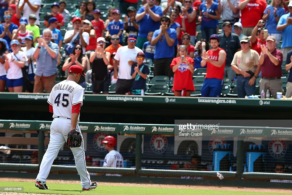 Fans cheer as <a gi-track='captionPersonalityLinkClicked' href=/galleries/search?phrase=Derek+Holland+-+Baseball+Player&family=editorial&specificpeople=8003703 ng-click='$event.stopPropagation()'>Derek Holland</a> #45 of the Texas Rangers leaves the mound after pitching in the seventh inning during a game against the Seattle Mariners at Globe Life Park in Arlington on August 19, 2015 in Arlington, Texas. The Texas Rangers defeated the Seattle Mariners 7-2.