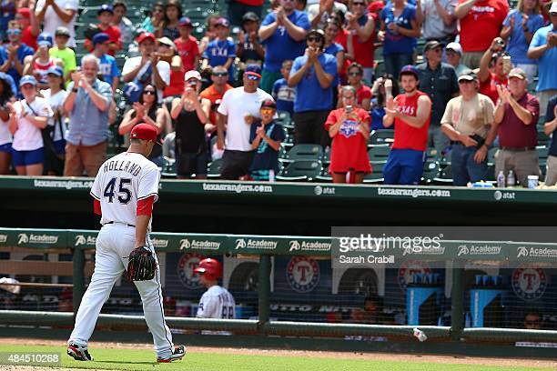 Fans cheer as Derek Holland of the Texas Rangers leaves the mound after pitching in the seventh inning during a game against the Seattle Mariners at...