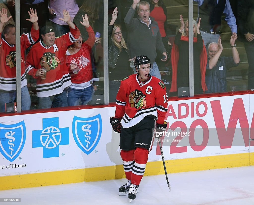 Fans cheer as <a gi-track='captionPersonalityLinkClicked' href=/galleries/search?phrase=Jonathan+Toews&family=editorial&specificpeople=537799 ng-click='$event.stopPropagation()'>Jonathan Toews</a> #19 of the Chicago Blackhawks celebrates a first period goal against the New York Islanders at the United Center on October 11, 2013 in Chicago, Illinois. The Blackhawks defeated the Islanders 3-2.