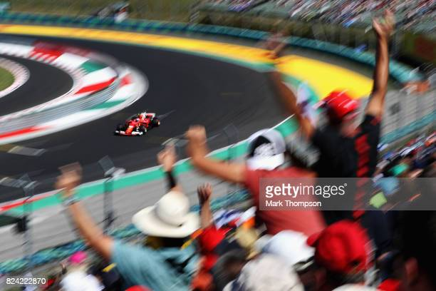 Fans cheer as Kimi Raikkonen of Finland driving the Scuderia Ferrari SF70H rounds the last corner during qualifying for the Formula One Grand Prix of...