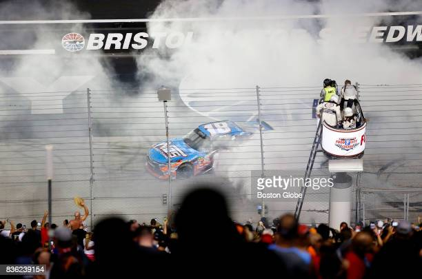 Fans cheer as Kyle Busch celebrates his the Bass Pro Shops NRA Night Race Qualifying Race win with a burnout at the Bristol Motor Speedway in Bristol...