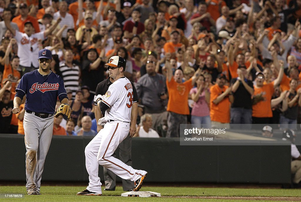 Fans cheer as <a gi-track='captionPersonalityLinkClicked' href=/galleries/search?phrase=Matt+Wieters&family=editorial&specificpeople=4498276 ng-click='$event.stopPropagation()'>Matt Wieters</a> #32 of the Baltimore Orioles pulls into third after a double and an error against the Cleveland Indians in the fifth inning at Oriole Park at Camden Yards on June 27, 2013 in Baltimore, Maryland. Two runs scored on the play. Also pictured is third baseman Lonnie Chisenhall #8 of the Cleveland Indians.
