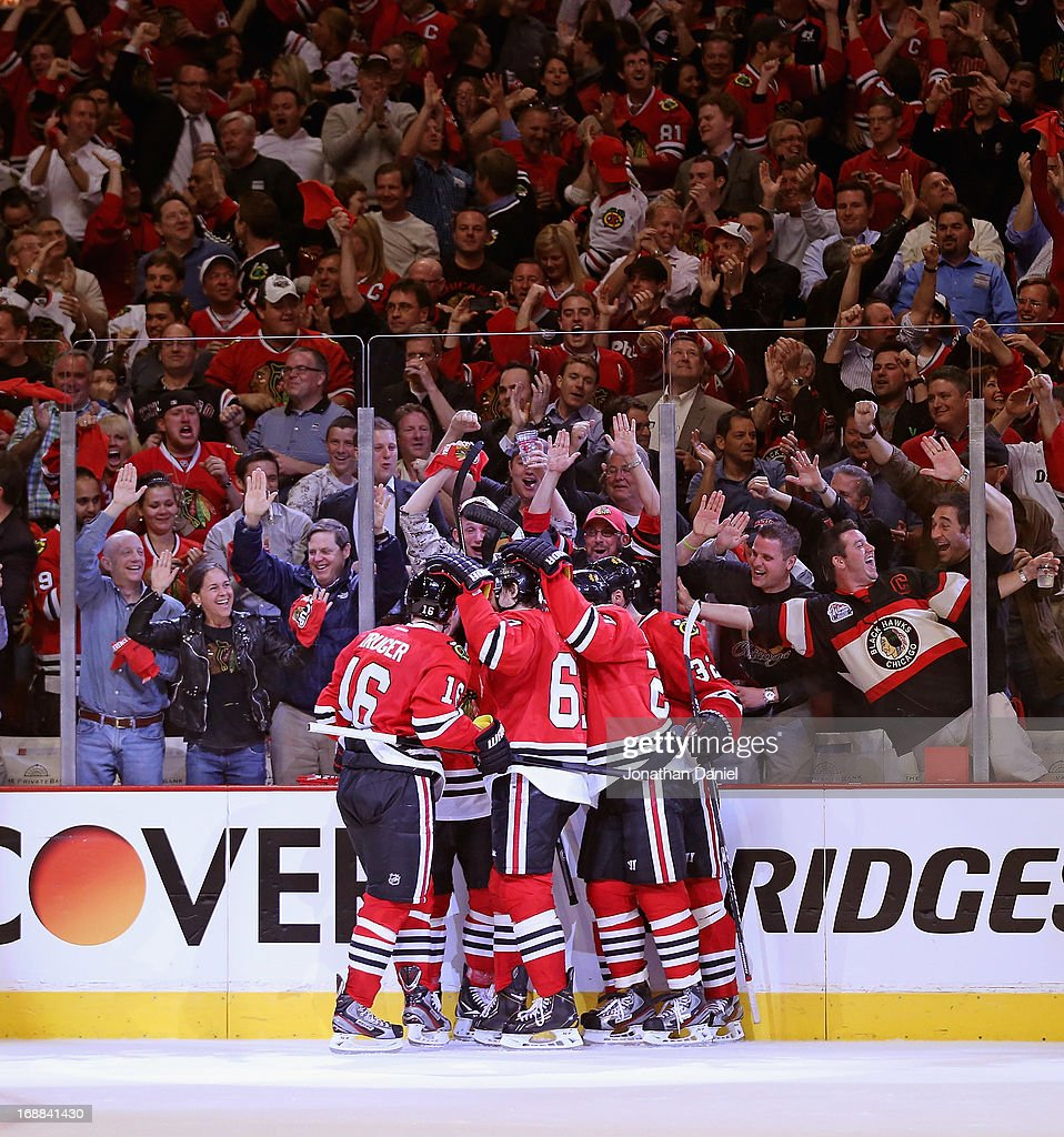 Fans cheer as members of the Chicago Blackhawks celebrate a third period goal against the Detroit Red Wings in Game One of the Western Conference Semifinals during the 2013 NHL Stanley Cup Playoffs at the United Center on May 15, 2013 in Chicago, Illinois. The Blackhawks defeated the Red Wings 4-1.