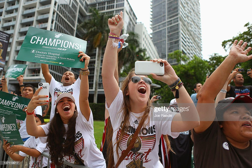 Fans cheer as Miami Heat players pass by in a victory parade through the streets during a celebration for the 2012 NBA Champion Miami Heat on June 25, 2012 in Miami, Florida. The Heat beat the Oklahoma Thunder to win the NBA title.