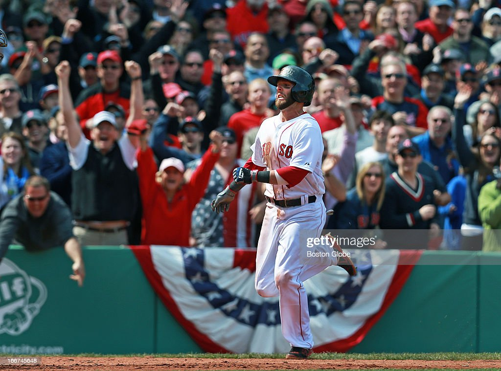 Fans cheer as the Red Sox's Dustin Pedroia heads for the plate with the game winning run in the bottom of the ninth inning. The Boston Red Sox hosted the Tampa Bay Rays in the annual Patriots Day morning matinee at Fenway Park.