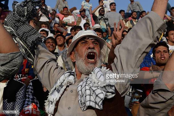 Fans cheer as their team enters the field before the start of the football match between Afghanistan and Pakistan at the Afghanistan Football...