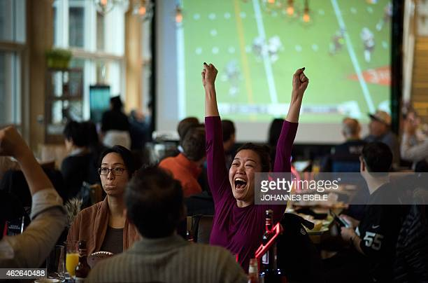 Fans cheer as they watch a live broadcast of Super Bowl XLIX between the New England Patriots and Seattle Seahawks at a restaurant in Shanghai on...