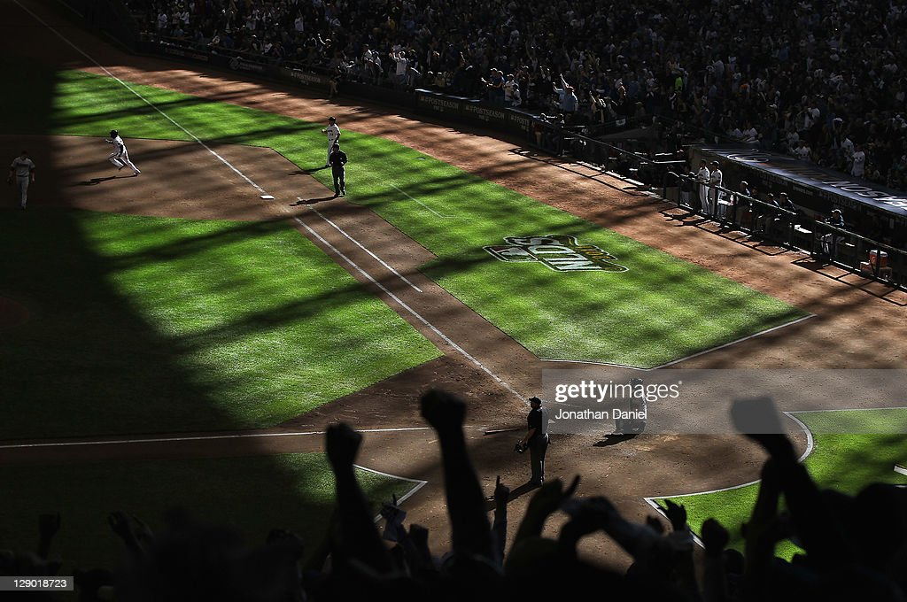 Fans cheer as Yuniesky Betancourt of the Milwaukee Brewers runs the bases after hitting a triple against the Arizona Diamondbacks during Game One of...