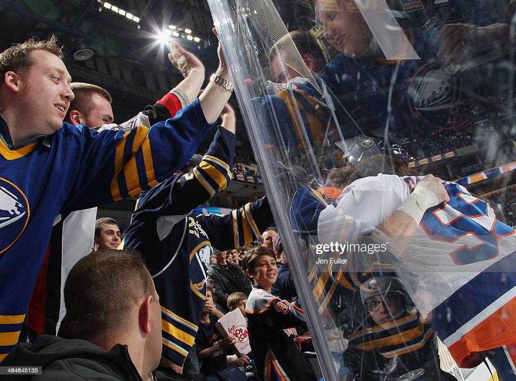 Fans cheer as Zenon Konopka #24 of the Buffalo Sabres fights Brett Gallant #59 of the New York Islanders at First Niagara Center on April 13, 2014 in Buffalo, New York.