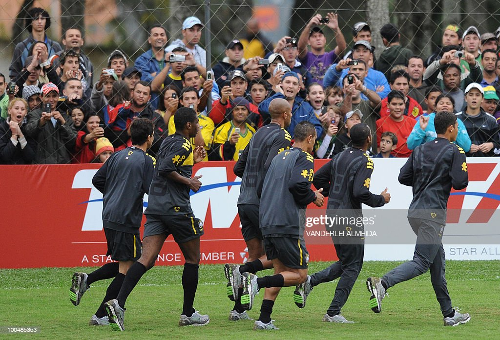 Fans cheer at the Brazilian players during a training session in Curitiba, southern Brazil on May 24, 2010. Brazil, five-time world champion, is among the favourites for the South Africa 2010 World Cup which starts on June 11th. The 'Selecao' have been drawn in Group G with North Korea, Ivory Coast and Portugal.
