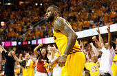 Fans cheer behind LeBron James of the Cleveland Cavaliers in overtime against the Atlanta Hawks during Game Three of the Eastern Conference Finals of...