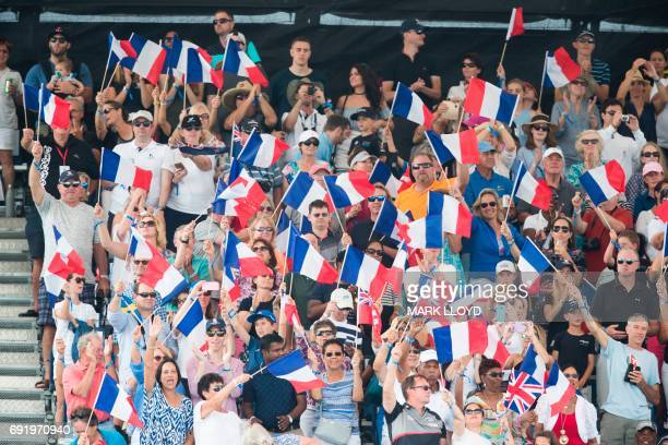 Fans cheer from the grandstand as Groupama Team France cross the finish line for the final time in the America's Cup on June 3 2017 on Bermuda's...