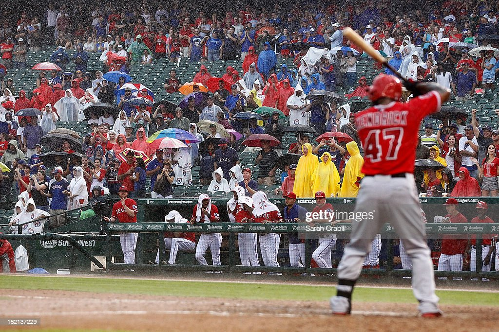 Fans cheer in the rain as <a gi-track='captionPersonalityLinkClicked' href=/galleries/search?phrase=Howie+Kendrick&family=editorial&specificpeople=628938 ng-click='$event.stopPropagation()'>Howie Kendrick</a> #47 of the Los Angeles Angels of Anaheim bats in the ninth inning during a baseball game against the Texas Rangers at Rangers Ballpark in Arlington on September 28, 2013 in Arlington, Texas. The Texas Rangers defeated the Los Angeles Angels of Anaheim 7-4.
