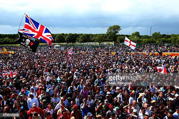 Fans cheer Lewis Hamilton of Great Britain and Mercedes GP after his victory in the Formula One Grand Prix of Great Britain at Silverstone Circuit on...