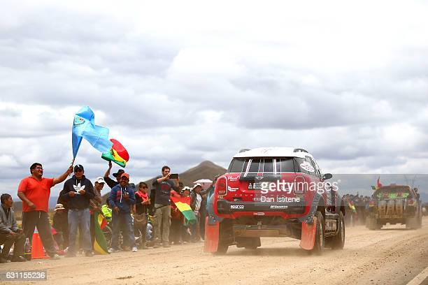 Fans cheer on Mikko Hirvonen of Finland and Mini XRaid and codriver Michel Perin of France in their John Cooper Works Rally Mini car as they depart...
